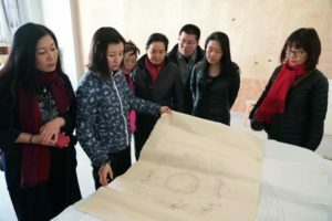 At the Dunhuang Research Academy inspecting a mural tracing.
