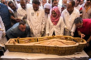Egypt's Antiquities Minister Khaled el-Enany (R), and Mostafa Waziri (L), the Secretary General of the Supreme Council of Antiquities, surround a sarcophagus belonging to a man in front the Hatshepsut Temple at the Valley of the Kings in Luxor on October 19, 2019. Egypt revealed today a rare trove of 30 ancient wooden coffins that have been well-preserved over millennia in the archaeologically rich Valley of the Kings in Luxor. The antiquities ministry officially unveiled the discovery made at Asasif, a necropolis on the west bank of the Nile River, at a press conference against the backdrop of the Hatshepsut Temple. Khaled DESOUKI / AFP.